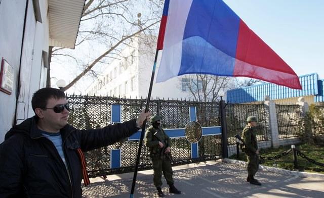 Mężczyźni trzymają rosyjskie flagi na Krymie /ZURAB KURTSIKIDZE /PAP/EPA