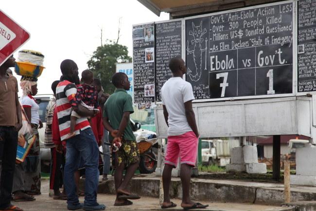 Mieszkańcy liberyjskiej Monrovii przy tablicy informacyjnej dot. eboli /PAP/EPA/AHMED JALLANZO /PAP/EPA
