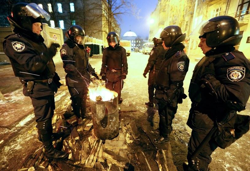 Milicjanci próbują się ogrzać w pobliżu budynku parlamentu /PAP/EPA