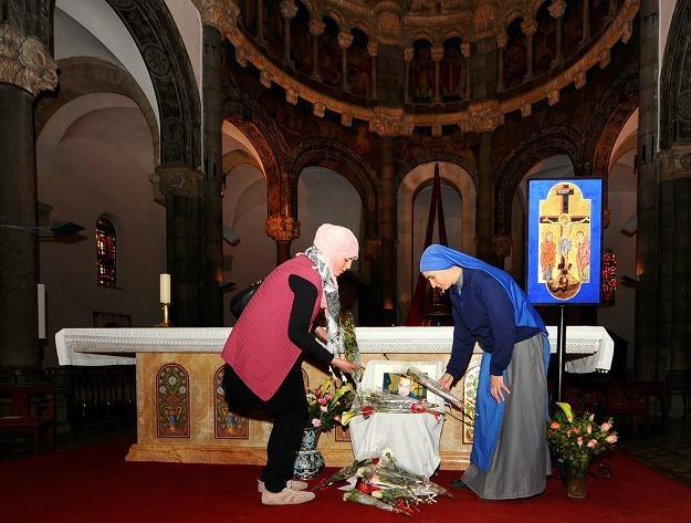 Muzułmanka i zakonnica układają kwiaty przed zdjęciem księdza Marka Rybińskiego /AFP