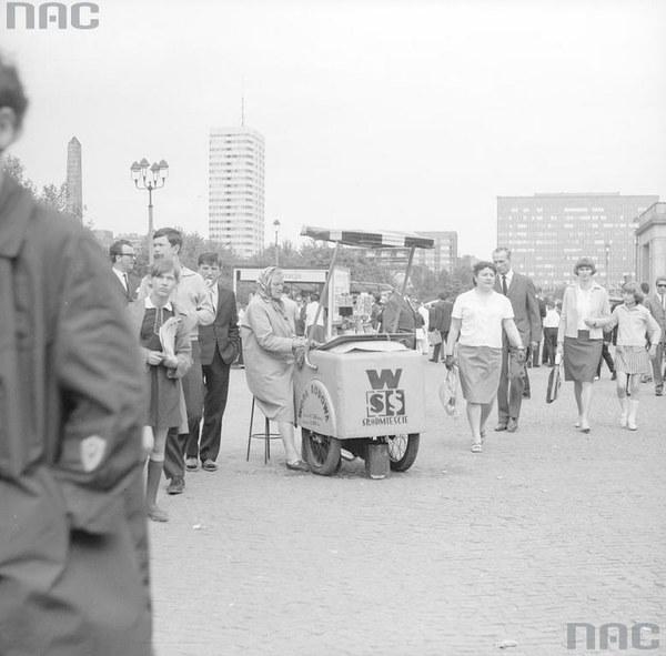 Uczestnicy kiermaszu książek w Warszawie. Widoczna kobieta sprzedająca wodę z saturatora wózkowego