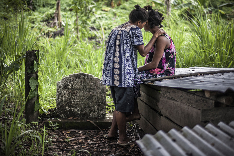 Na zdjęciu dwie Papuaski nad grobem swojej starszej siostry // VLAD SOKHIN / CHILDFUND AUSTRALIA /AFP