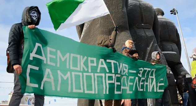 """Na zdjęciu flaga Syberii i napis: """"Demokracja to prawo do samostanowienia"""" /"""