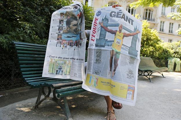 """Na zdjęciu kobieta czyta dzisiejszy numer """"l'Equipe"""". Paryż, 26 lipca 2012 /AFP"""