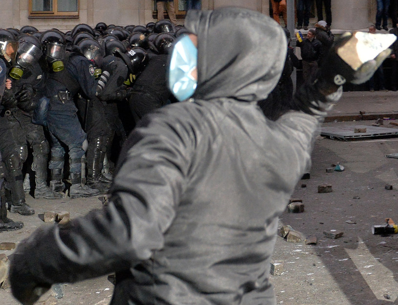 Na zdjęciu protestujący rzuca kamieniem w policję /SERGEI SUPINSKY /AFP