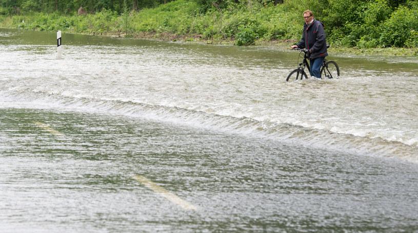 Na zdjęciu rowerzysta pokonuje zalaną ulicę w Hannoverze /ULIAN STRATENSCHULTE /AFP
