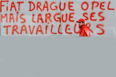 """Napis na murze: """"Flirtując sie z Oplem  Fiat wyrzuca swoich pracowników"""". /AFP"""