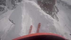 Narciarz zjeżdża wzdłuż szczytu w górach
