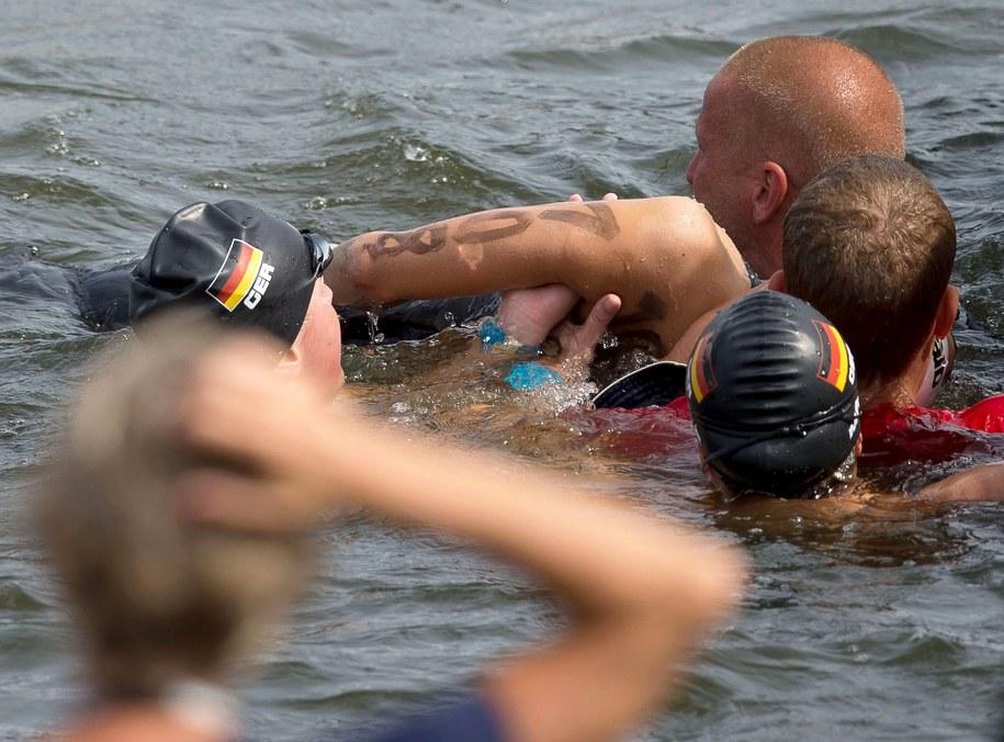 Niemieccy pływacy Finnia Wunram i Angela Maurer asystują ratownikom przy wyciąganiu Natalii Charłos z wody /TIM BRAKEMEIER /PAP/EPA