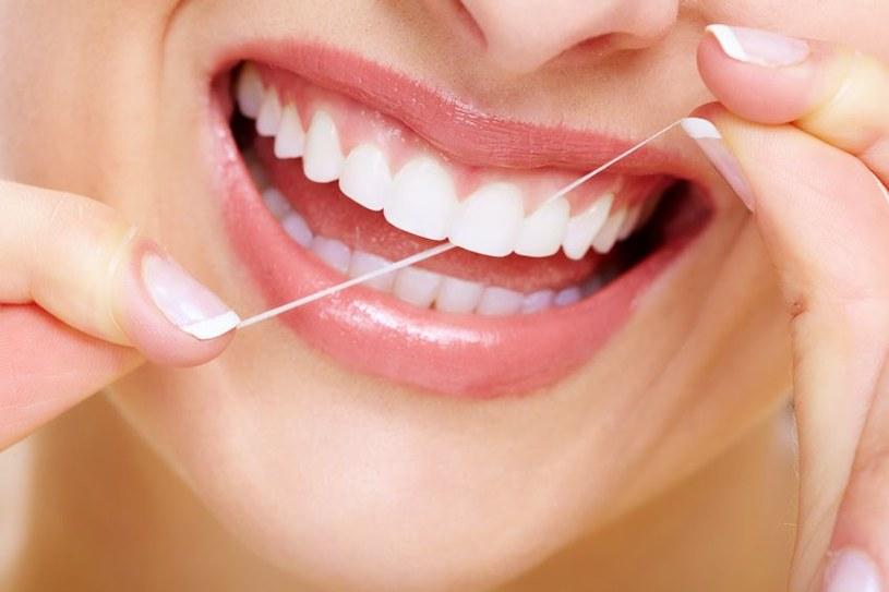 Nieprawidłowe korzystanie z nici dentystycznej uszkadza zęby /123RF/PICSEL