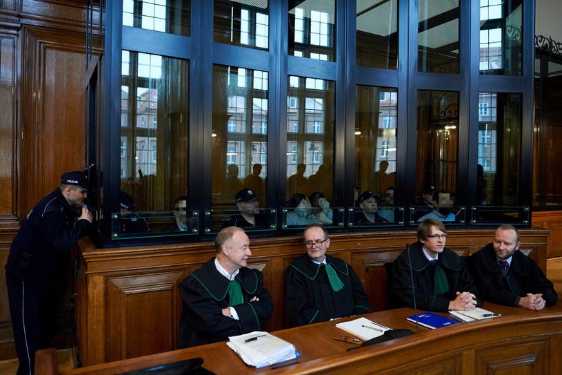 Oskarżeni (za szybą) o udział w zorganizowanej grupie przestępczej zajmującej się sutenerstwem oraz ich adwokaci /Adam Warżawa /PAP