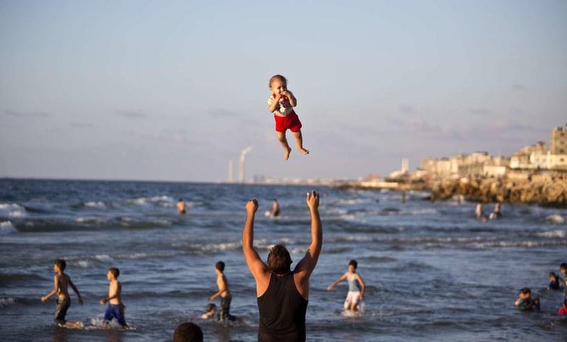 Palestyńczyk bawi się z dzieckiem na plaży (Gaza, wrzesień 2014) /AFP