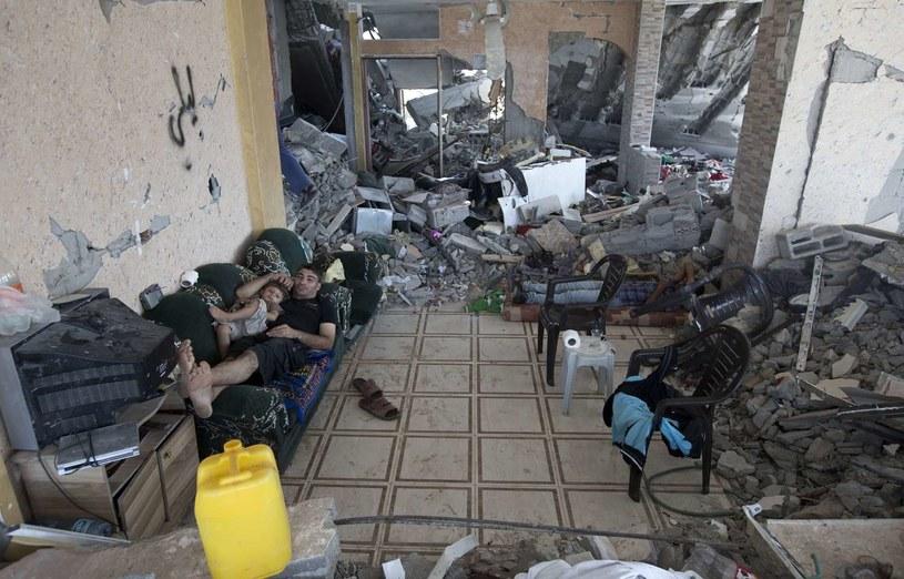 Palestyńczyk z synem wypoczywa po powrocie do swojego zniszczonego domu... /AFP