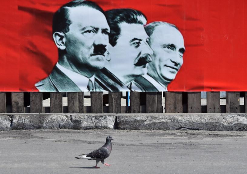 Plakat zestawiający wizerunek Putina ze Stalinem i Hitlerem na placu Niepodległości w Kijowie /SERGEI SUPINSKY /AFP