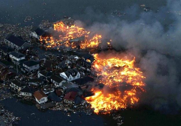 Płonące domy po przejściu fali tsunami w Natori /AFP
