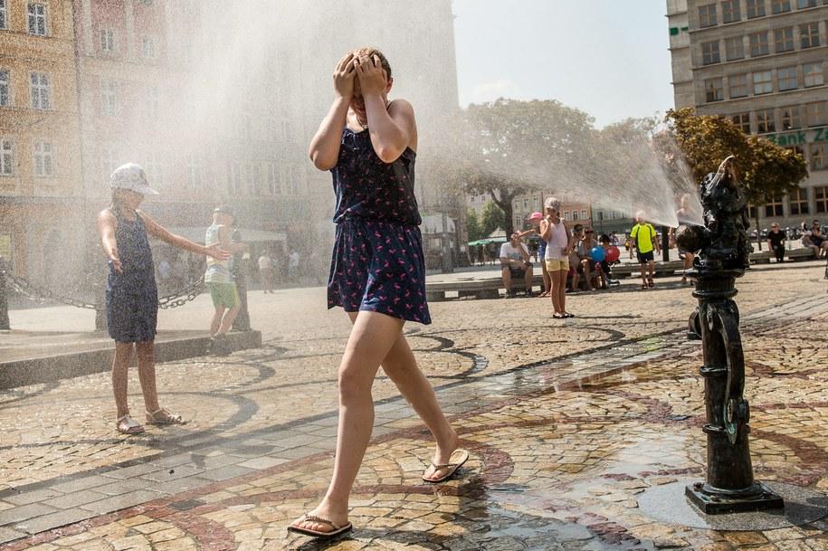 Podczas trwających upałów wrocławianie oraz turyści korzystają z ochłody przy kurtynie wodnej na rynku we Wrocławiu /Maciej Kulczyński /PAP