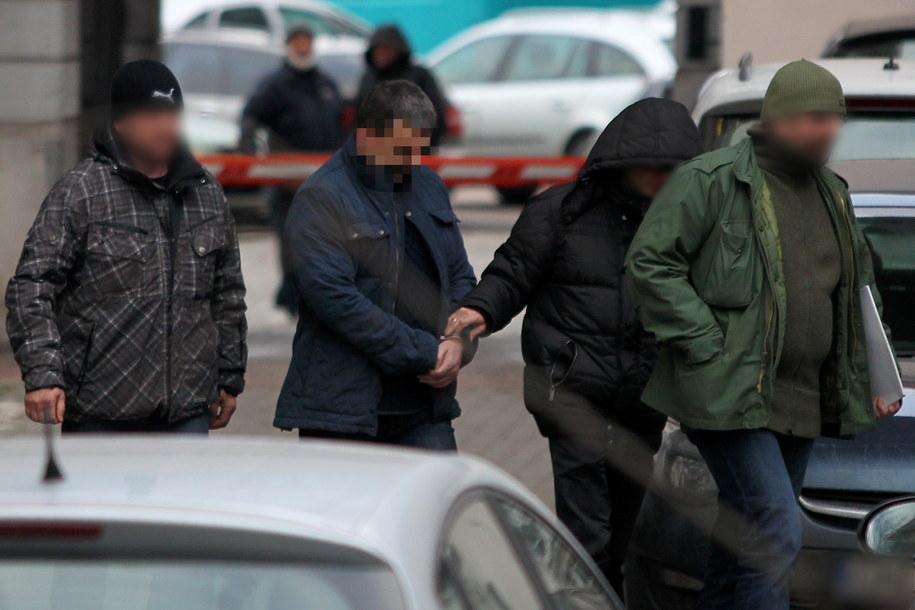 Policjanci wyprowadzają z gdańskiej prokuratury jednego z podejrzanych (2L) w sprawie parabanków /Piotr Wittman /PAP