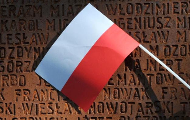 Polska flaga na tle pomnika pomordowanych przez Sowietów polskich oficerów w Charkowie /AFP