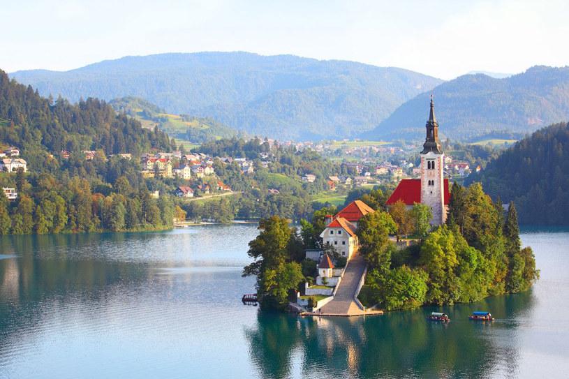 """Popłyń łodzią na wyspę na jeziorze Bled, opisywanym przez narodowego poetę jako """"drugi Eden, pełen czaru i uroku"""", gdzie sprzed kościoła rozpościera się jeden z najpiękniejszych widoków na Alpy. /123RF/PICSEL"""