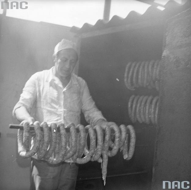 Pracownik masarski z kiełbasą w wędzarni /Z archiwum Narodowego Archiwum Cyfrowego