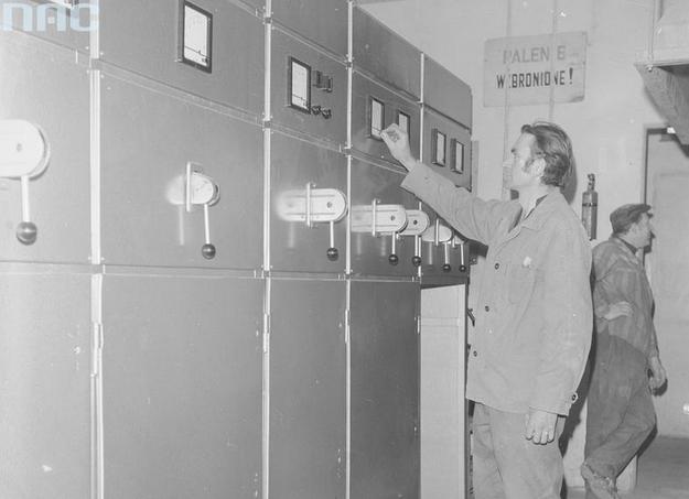 Pracownik przy rozdzielni elektrycznej. Widoczne mierniki tablicowe (zdjęcie ilustracyjne) /Z archiwum Narodowego Archiwum Cyfrowego