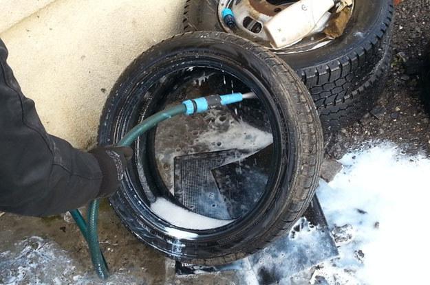 Pracownik serwisu usuwa wężem z wodą płyn uszczelniający z wnętrza opony. /INTERIA.PL