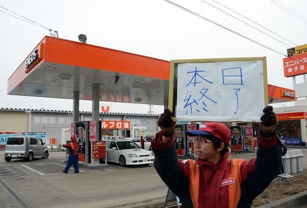"""Pracownik stacji trzyma tabliczkę z napisem: """"Brak paliwa"""" /AFP"""
