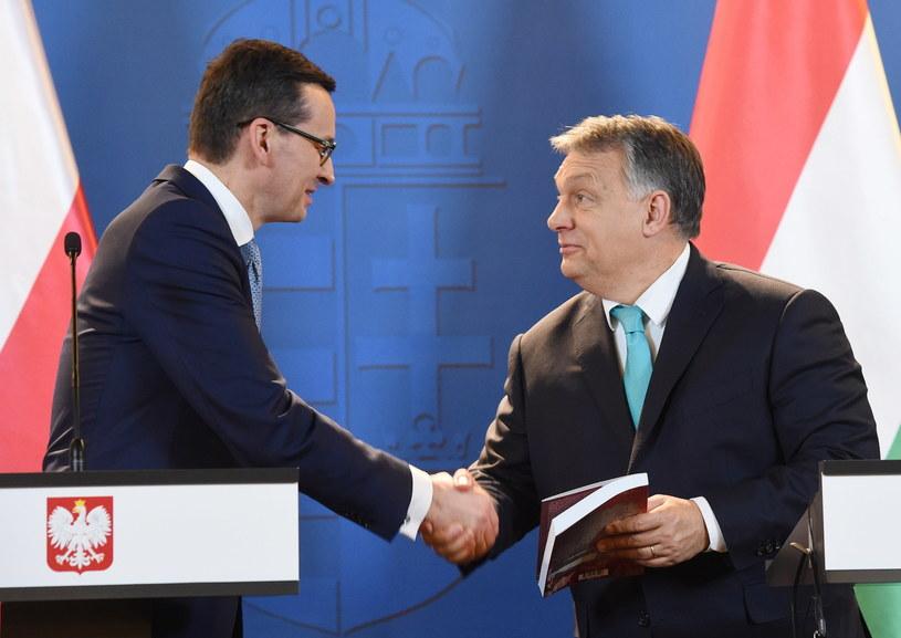 Premier Mateusz Morawiecki przekazuje premierowi Węgier Viktorowi Orbanowi książkę o Solidarności Walczącej podczas konferencji prasowej po spotkaniu w Budapeszcie /Radek Pietruszka /PAP