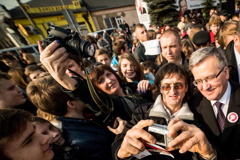 Prezydent Bronisław Komorowski (P) pozuje do wspólnego zdjęcia, podczas spotkania z wyborcami na rynku w Aleksandrowie Kujawskim /Tytus Żmijewski /PAP