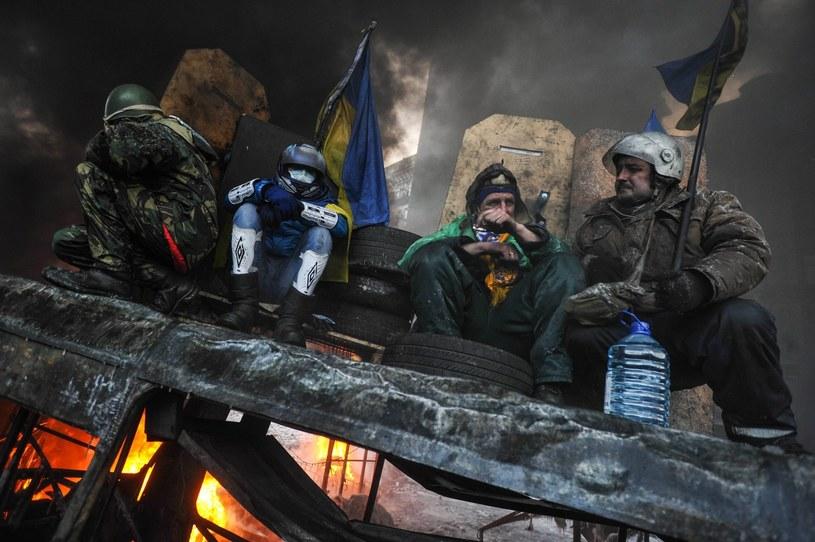 Przeciwnicy rządu siedzą na dachu spalonego autobusu w Kijowie /PAP/EPA
