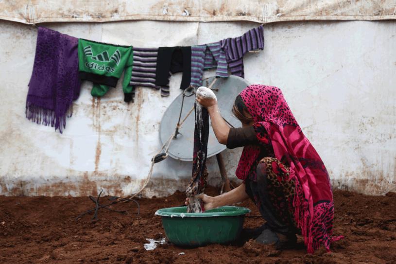 Przesiedlona syryjska kobieta z prowincji Idlib robi pranie w prowizorycznym obozie w pobliżu miasta Azaz w północnej Syrii /AFP
