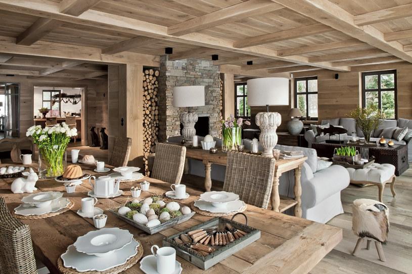 Przestronny salon połączony z jadalnią. Sufit, ściany i podłoga wyłożone są dębowymi deskami. Stylowe, ozdobne meble zrobiono z tego samego drewna. Niektóre pobielono, żeby harmonizowały z szarawym kolorem łupka, którym obłożony jest kominek /Rafał Lipski /Twój Styl