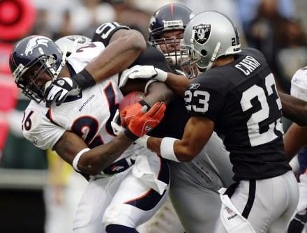 Raiders-Broncos 13-17.Tatum Bell zatrzymywany przez graczy z Oakland: Chrisa Carra i Terdella Sandsa /AFP