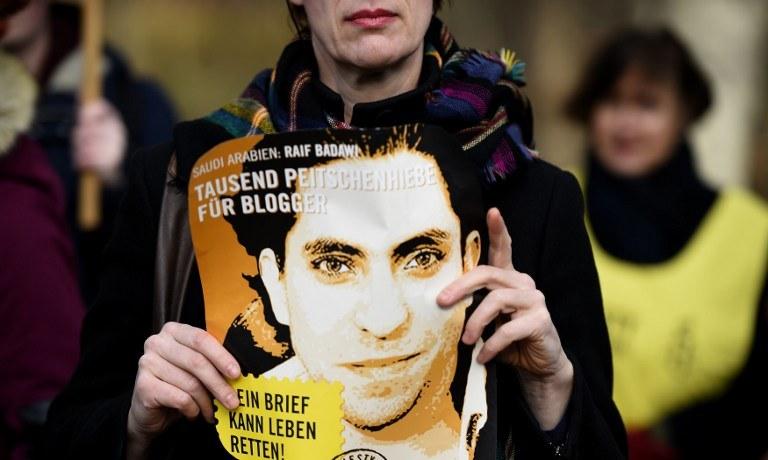 Raif Badawi na plakacie protestującej kobiety /AFP