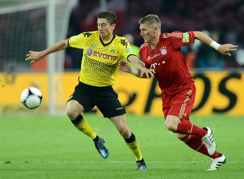 Robert Lewandowski (Borussia) w walce z Bastianem Schweinsteigerem (Bayern) /AFP