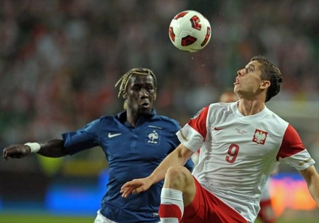 Robert Lewandowski (z prawej) w walce z Bacarym Sagną z reprezentacji Francji /AFP