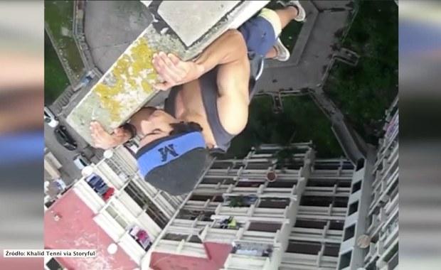Robi pompki... zwisając z dachu budynku