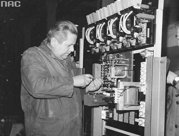 Robotnik podczas pracy przy rozdzielni elektrycznej. Widoczne gniazda bezpieczników i stos prostowniczy (zdjęcie ilustracyjne) /Z archiwum Narodowego Archiwum Cyfrowego