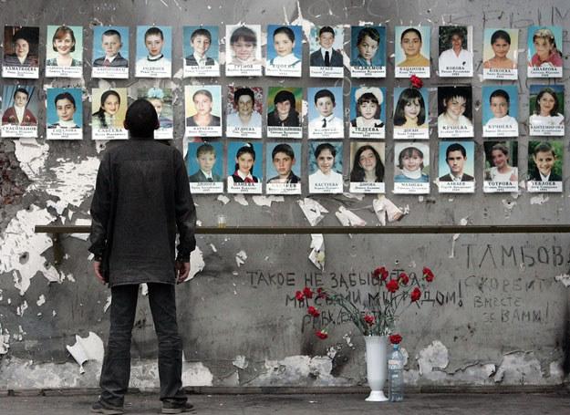 Ruiny szkoły w Biesłanie. Mężczyzna ogląda zdjęcia ofiar /YURI KADOBNOV/ AFP /East News