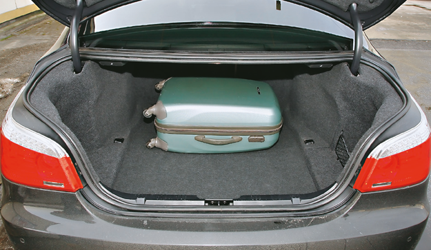 SEDAN (E60) Klapa jest szeroka, co ułatwia załadunek dość płytkiego bagażnika o pojemności 520 litrów. Tuż pod linią szyby są dźwignie, którymi można zwolnić blokady tylnego oparcia. /Motor