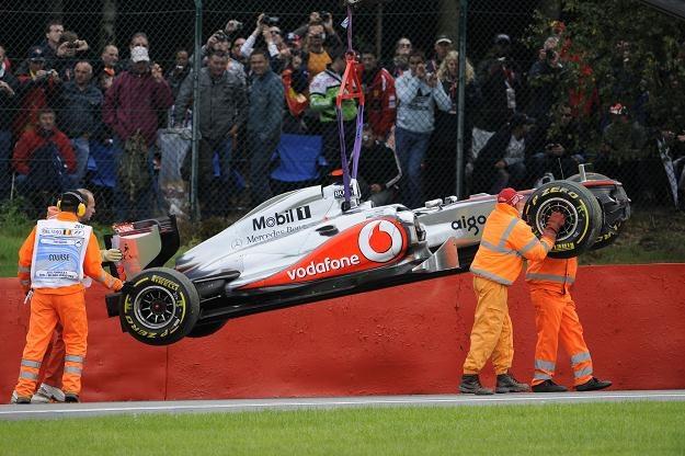 Służby porządkowe usuwają rozbity bolid Lewisa Hamiltona /AFP