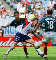 Strzelec pierwszego gola dla USA McBride (w środku) w kleszczach obrońców
