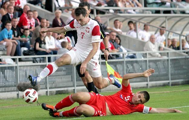Szarżujący z piłką Michał Kucharczyk (L) przeskakuje nad Tarasem Burlakiem fot: Piotr Polak /PAP