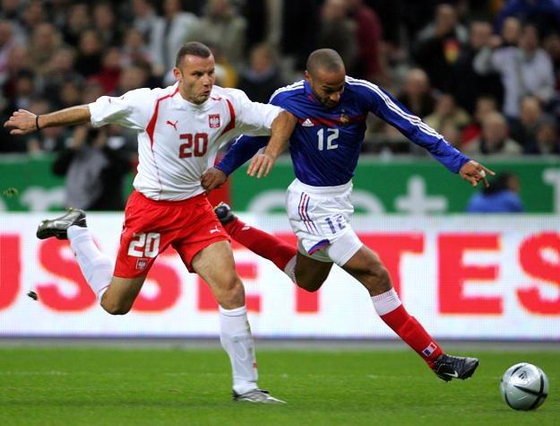 Tomasz Kłos walczy z Thierrym Henrym podczas meczu Francja - Polska  17 listopada 2004 r. /AFP