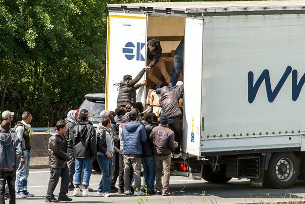 Uchodźcy wskakują do ciężarówki jadącej w kierunku kanału La Manche /AFP