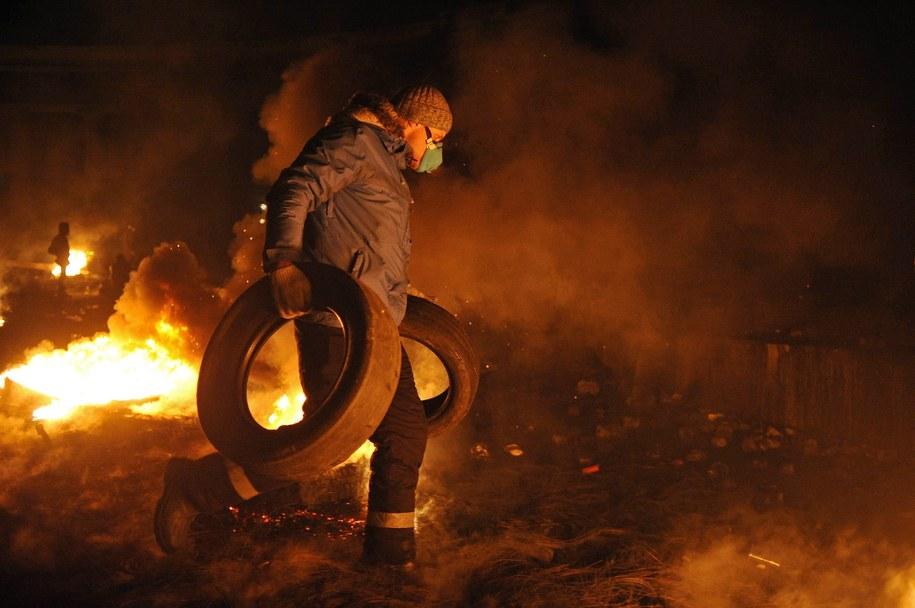 Uczestnik protestów dorzuca do ognia opony /ALEXEY FURMAN /PAP/EPA
