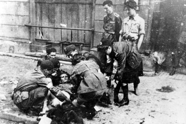 Udzielanie pomocy rannemu powstańcowi na ulicy /Z archiwum Narodowego Archiwum Cyfrowego
