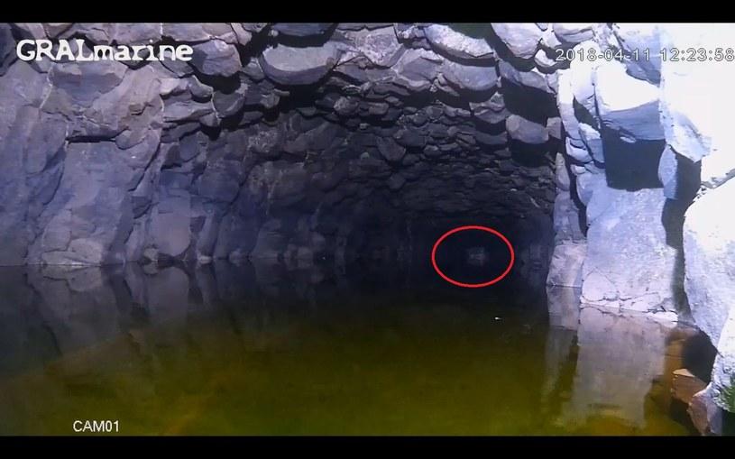 W czerwonej ramce zaznaczony w głębi korytarza obiekt – prawdopodobnie wózek górniczy lub... skrzynie /Odkrywca