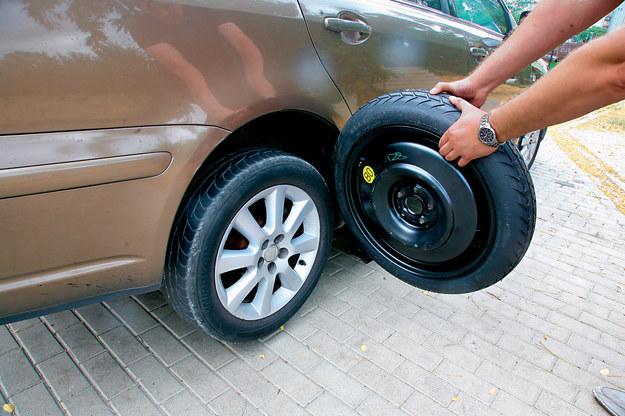 """W niektórych autach (np. Ford Mondeo) po odkręceniu śrub, mogą być trudności ze zdjęciem koła. Zamiast w nie kopać, lepiej uderzyć """"rozbujanym"""" zapasem. /Motor"""