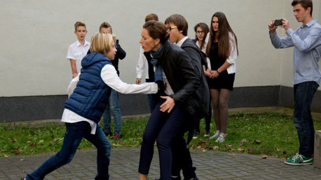 W ostatniej chwili Kajtka zasłania własnym ciałem dyrektorka gimnazjum. Pawłowicz zostaje ugodzona nożem! /www.barwyszczescia.tvp.pl/